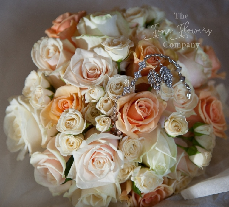 Great Fosters autumn wedding - bridal bouquet of ivory, cream, gold and peach roses