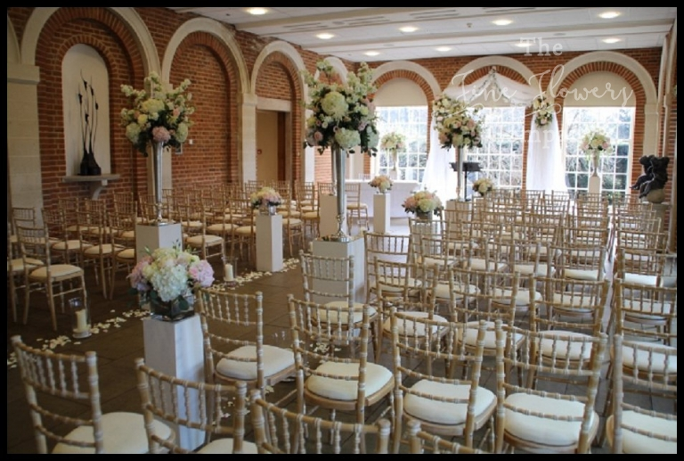 wedding ceremony flowers at Great Fosters. Tulle voile draping. Chiavaro chairs.
