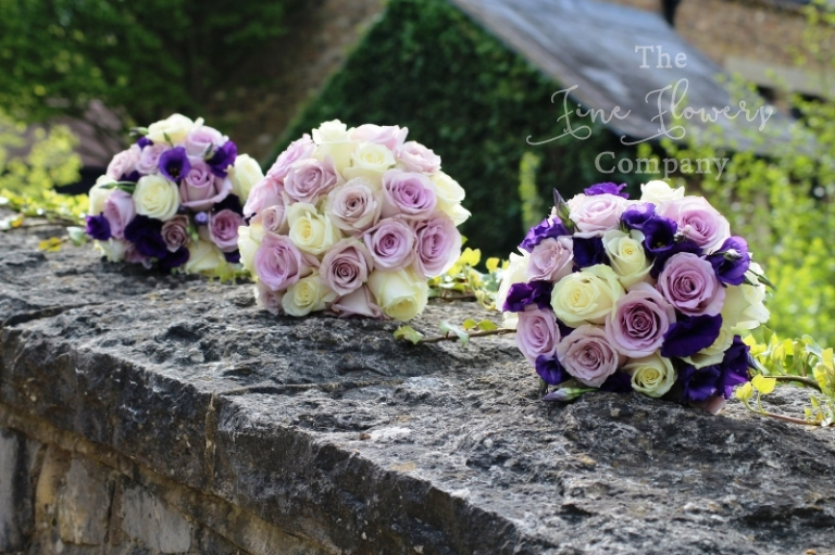 Bridal and bridesmaids bouquets photos from Coworth Park wedding, ivory, lilac and deep purple bouquets