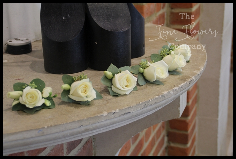 white rose buttonholes with silver green eucalyptus.