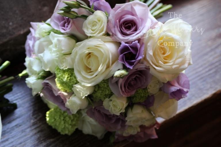 Bridesmaids bouquet of lilac roses, lisianthus and vibernum, from Great Fosters wedding in Surrey