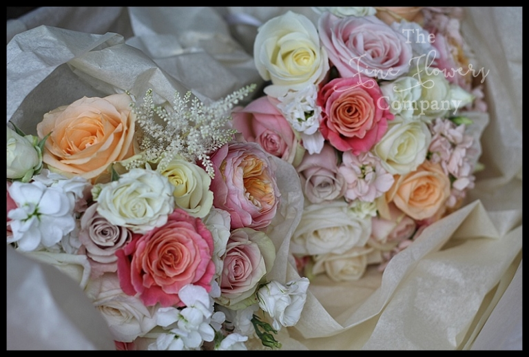 ivory cream, nude pink, peach and coral bridesmaids bouquets of roses and scented stocks.