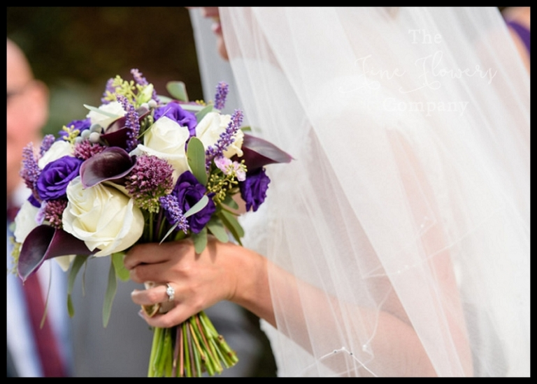bridal handtied bouquet of ivory Avalanche roses, purple lisianthus, plum purple calla lilies, plum muscari and silver eucalyptus.