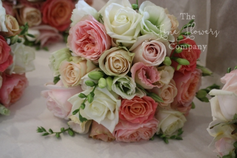 bridal bouquet of ivory, pale pink, peach and coral roses, with vuvuzuella roses and miss piggy roses.