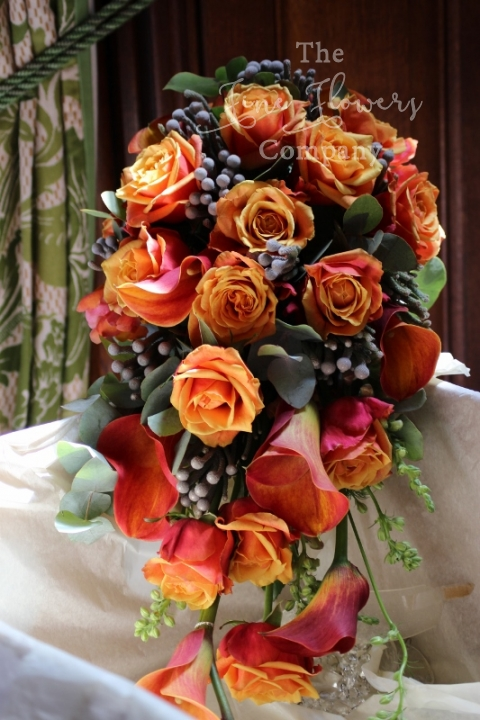 bridal bouquet of orange calla lilies, silver brunnia berries and Cherry Brandy roses