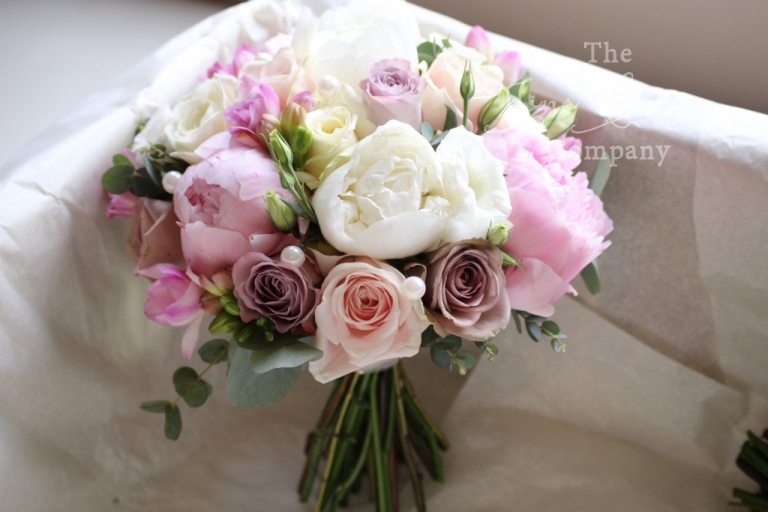 Bridal bouquet of paeonies, pale pink roses and Amnesia roses, with freesias and pearls. From Botleys Mansion wedding reception