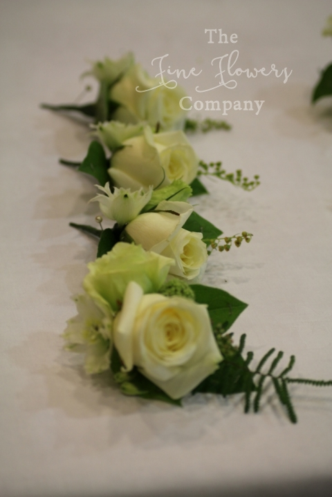 ivory Avalanche rose buttonholes with lisianthus, coral fern and oregano herbs