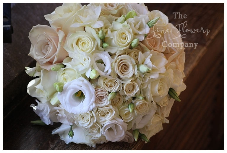white and cream ivory bridal bouquet of roses, spray roses, lisianthsu and freesias with vendetta and avalanche roses