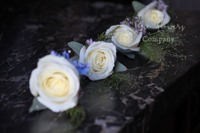 ivory rose buttonholes with blue delphinium and wax flowers and panic grass.