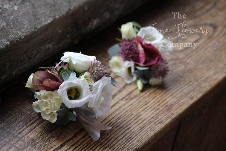 corsages of ivory lisianthus, heleborus and dusky pink astrantia from recent wedding at Great Fosters