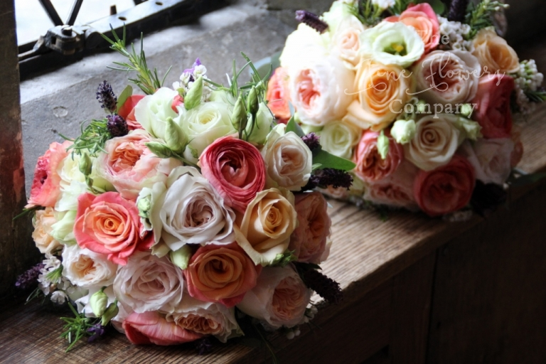 coral wedding flowers at Great Fosters in surrey, bridal bouquets of ivory, cream, blush and coral.