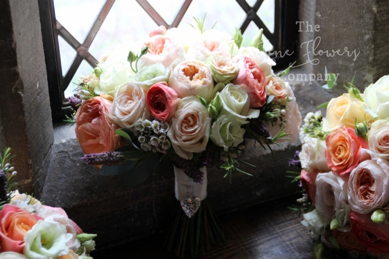 bridal bouquet of coral David Austin rose,s vuvuzuela roses, O'Hara roses, ivory cream and coral, from wedding at Great Fosters