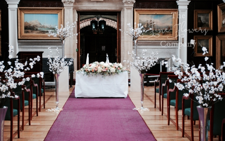 Wedding ceremony in the picture gallery at Royal holloway. Tall silver vases with cherry blossom.
