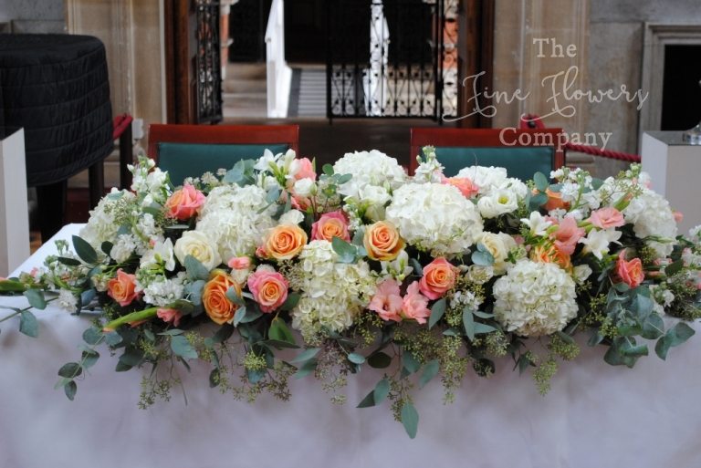 ceremony tabe wedding flowers in ivory and coral from wedding ceremony at Royal Holloway in the Picture Gallery
