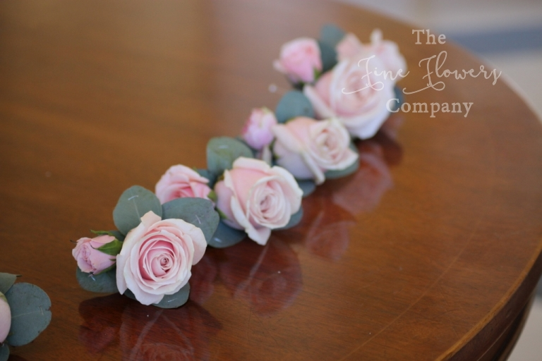 pale pink rose buttonholes with silvery green eucalyptus leaves.
