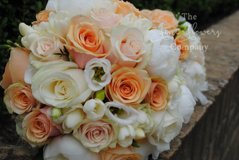 bridal boquuet of ivory, cream and pale peachy gold roses, with ivory white paeonies and white scented freesias and spray roses. From pembroke lodge wedding