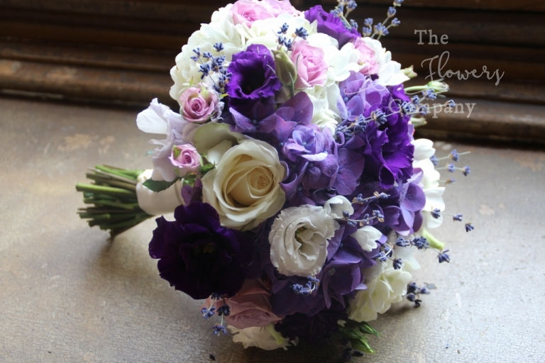 ivory purple bridal bouquet with ivory roses and spray roses, blush pink spray roses, hydrangeas, purple lisianthus and lavender, from wedding at Highclere castle