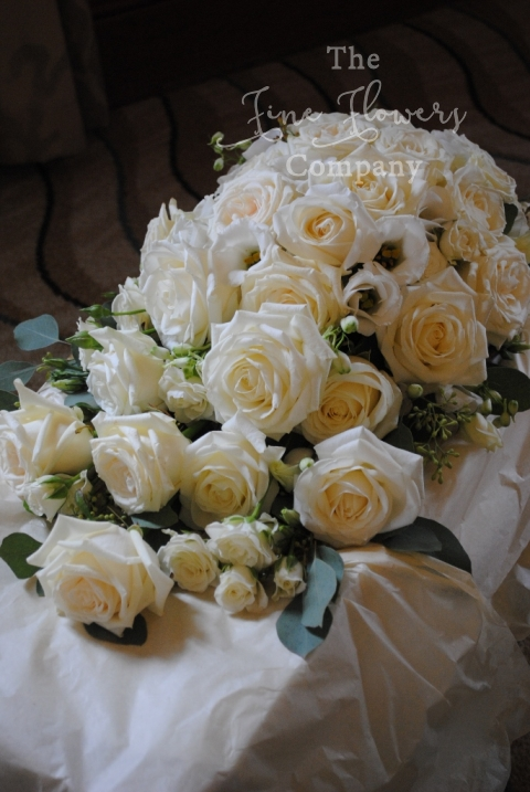 tear drop bouquet of ivory Avalanche, Dolimity roses, spray roses and lisianthus, with silvery green eucalyptus foliage. From wedding reception at Pennyhill Park. Pennyhill Park wedding flowers. Pennyhill park wedding.