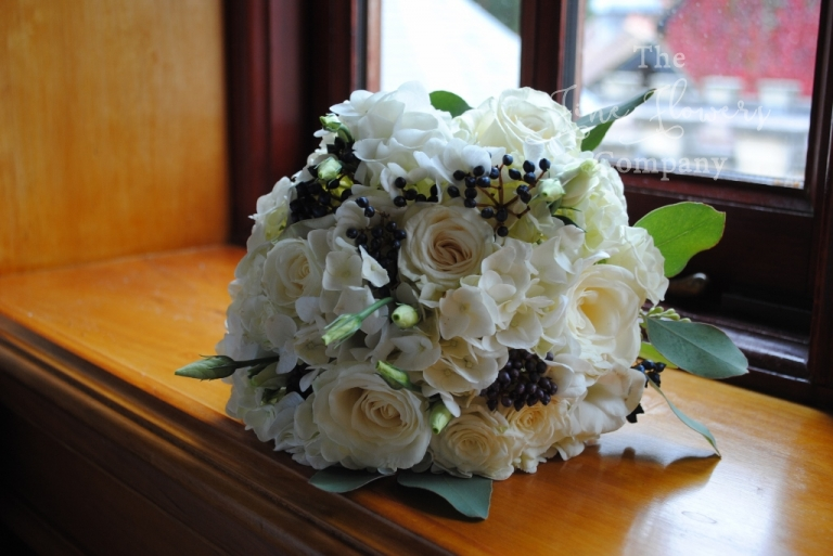 ivory and dark navy black wedding flowers. Bridesmaids bouquet of roses, hydrangeas, vibernum berries.