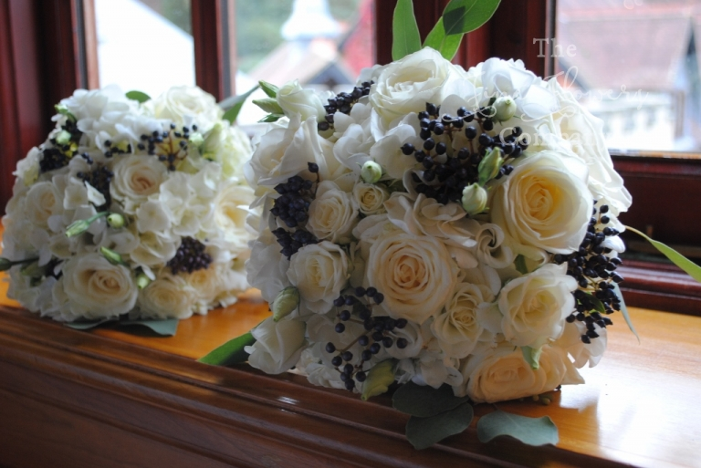 bridesmaids bouquet of avalanche roses, hydrangeas, lisianthus and dark midnight blue black bibernum berries. From wedding reception at Pennyhill Park. Pennyhill Park wedding flowers. Pennyhill park wedding.