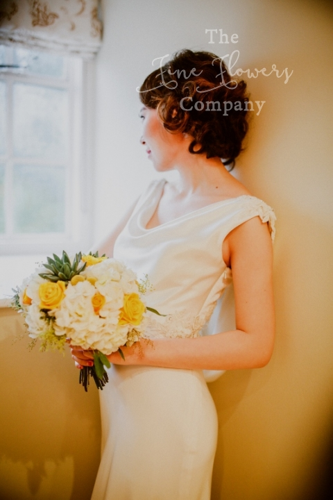 bridal bouquet of ivory hydrangea, yellow roses and succulents.