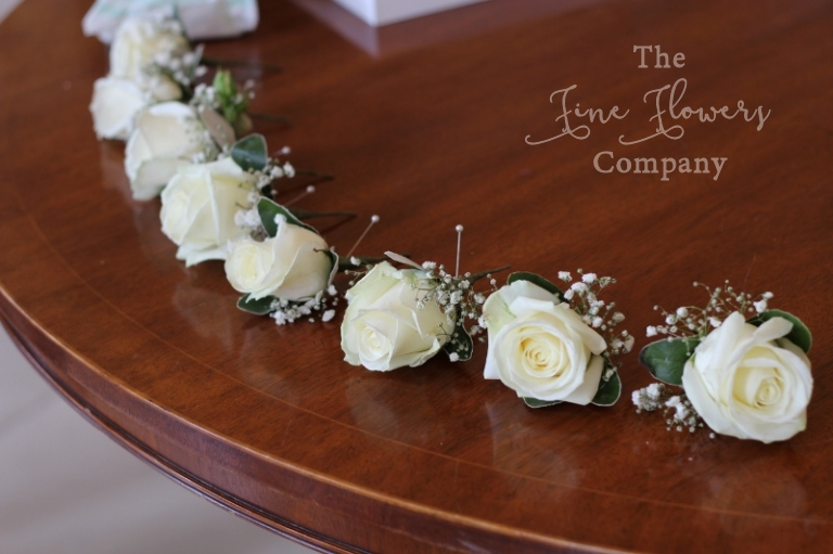 Avalanche rose buttonholes with gypsophila babys breath.