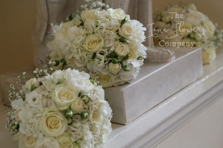 bridal bouquet and bridesmaids bouquets of ivory Avalanche roses, paeonies, spray roses, lisianthsu and gypsophila, from wedding at Botleys Mansion. Bijou wedding flowers, Bijou wedding florist.