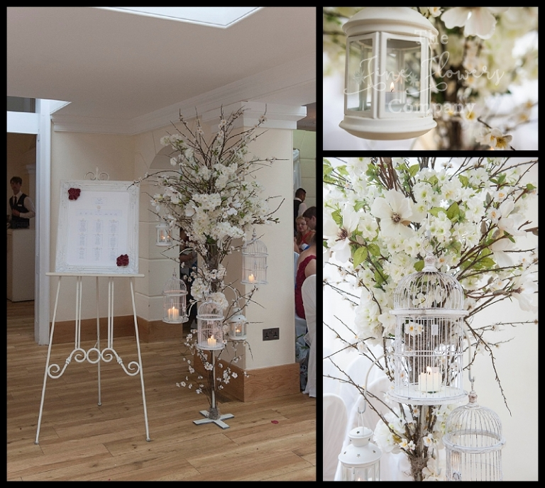 tall wedding flowers trees floor standing centrepiece with hanging lanterns and tea light holders and bird cages.
