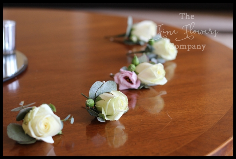 ivory avalanche rose buttonholes with blush pink lisianthus and silver sage green eucalyptus leaves.