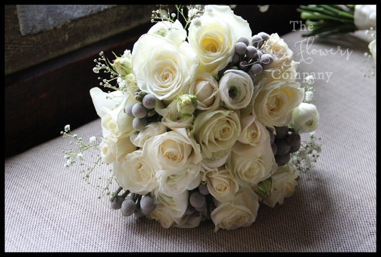 winter white rose bouquet with white ranunculus, roses, lisianthus, silver grey brunnia berries