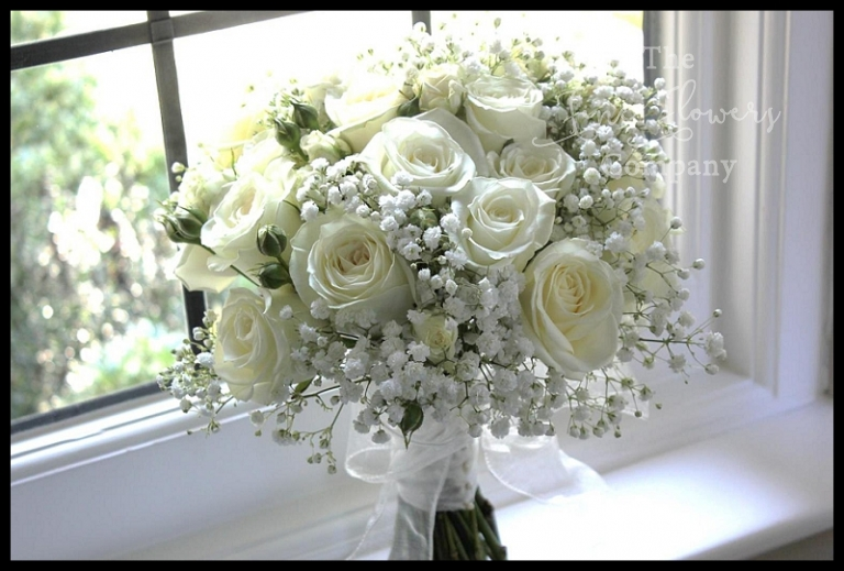 bridal handtied bouquets of white roses ivory roses and gypsophila babys breath.