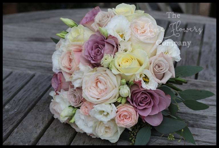 handtied bridal bouquet of ivory avalanche roses, hint of pink Ohara roses, pale pink Bombastic roses, pale lilac Safi roses and pinky lilac memory lane roses, with lisianthus. bridal flowers surrey, pink lilac bridal bouquet.