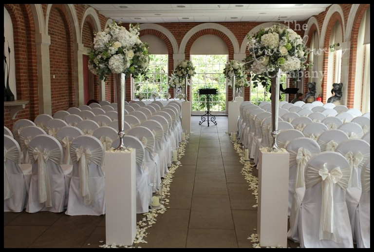 great fosters wedding ceremony in the Orangery. White wedding flowers starting and ending the wedding aisle. TRall silver vase displays on plinths, wedding ceremony at Great Fosters, Great Fosters florist.