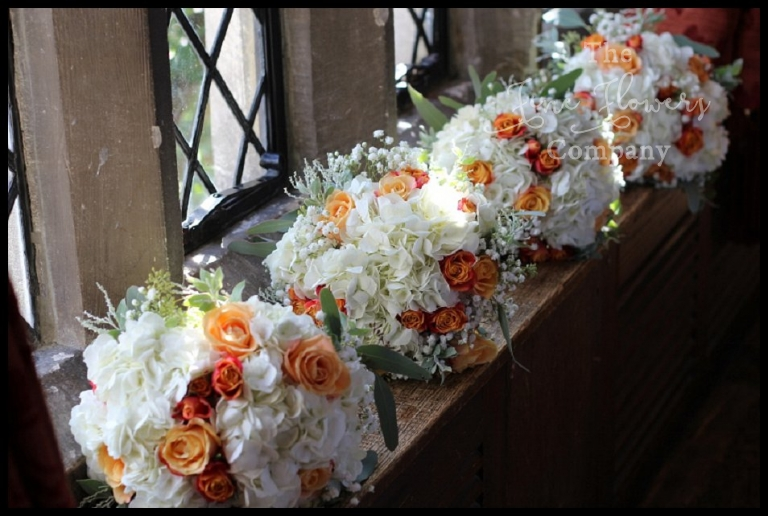 ivory and orange bridesmaids bouquets with hydrangeas, roses and gypsophila