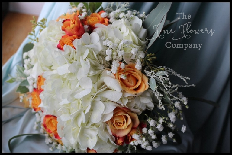 ivory and orange bridesmaids bouquet of hydrangea, orange roses, gypsophila and silver mimosa