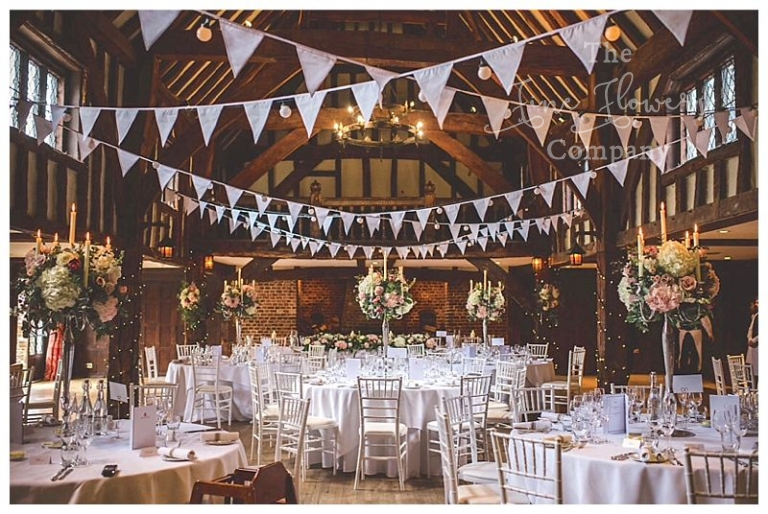 Great Fosters tithe barn reception, bunting, candelabras.