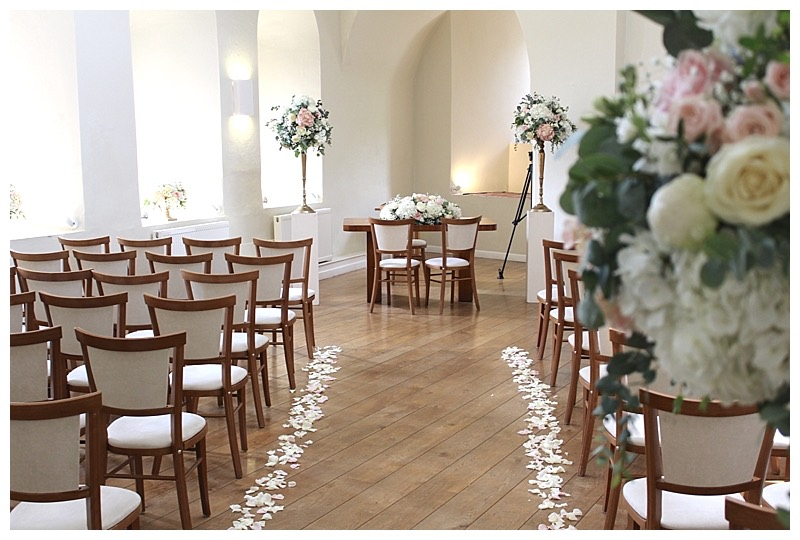 rose petals scatter down teh aisle at Farnham Castle.