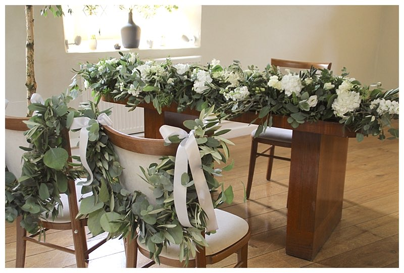 silvery sage green eucalyptus chair swags and table runner with wild organic display, from wedding at Farnham castle.