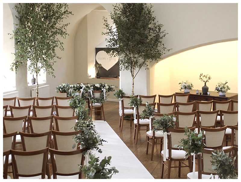 botanical outdoorsy wedding ceremony with silver birch trees and foliage chair ends posies. From wedding at Farnham castle.