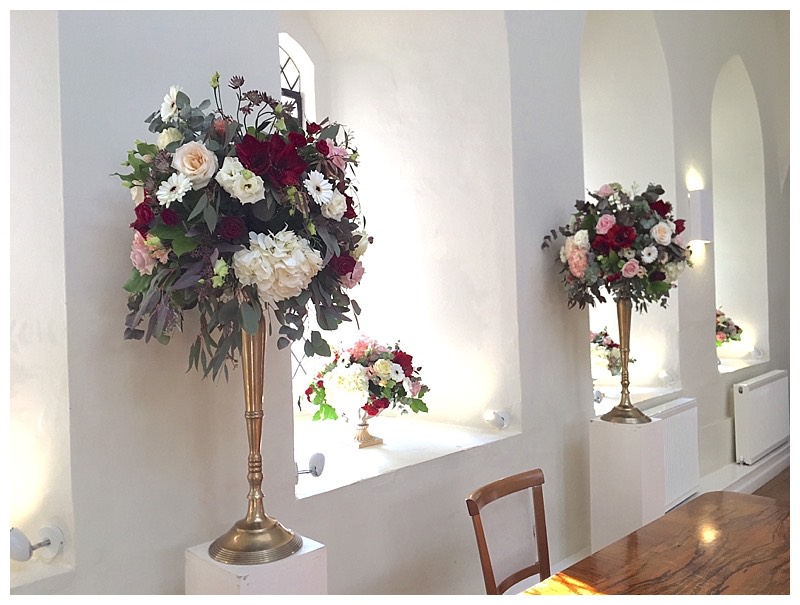 ceremony flowers at farnham castle burgundy wedding