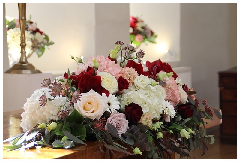 ceremony table centrepiece with ivory and blush hydrangeas and roses, burgundy amaryllis and eucalyptus.