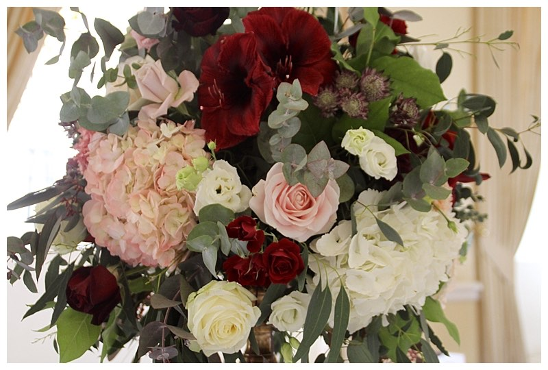 burgundy and blush and crea, wedding flowers centrepiece with hydrangeas, roses and burgundy amaryllis.