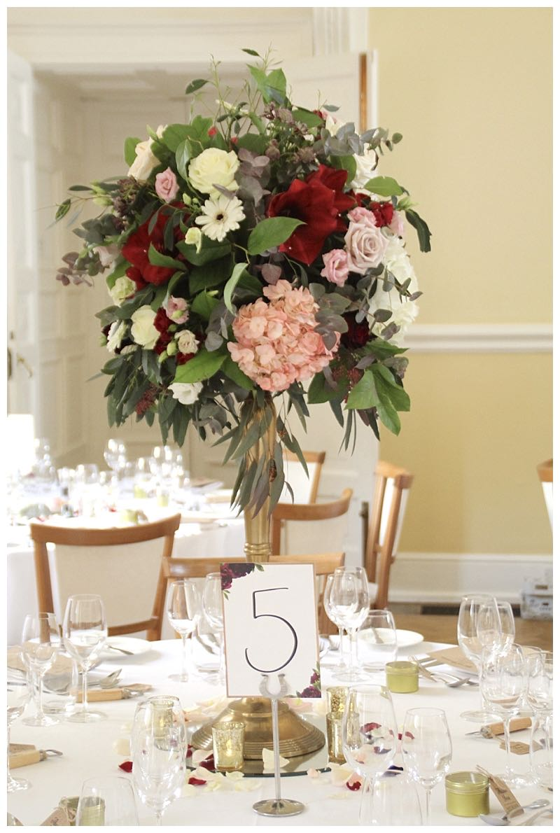 Farnham Castle burgundy pink and ivory area, wedding table centrepieces, gold candelabra centrepiece with hydrangea, amaryllis, roses and gerberas,