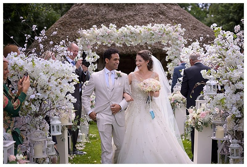 surrey barn wedding flowers - wedding ceremony aisle with flower trees and floral arch at Great Fosters in Surrey.