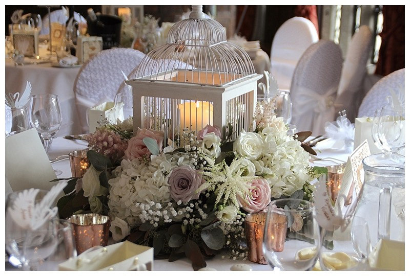 surrey barn wedding flowers - bird cage centrepiece in the tithe barn at Great Fosters