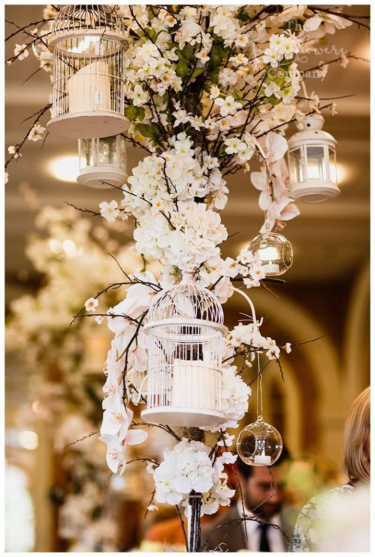 tall blossom and lanterns and candles flowers trees centrepieces.