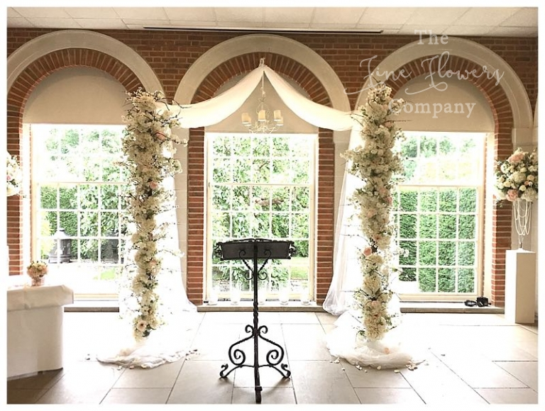 wedding canopy arch with draping tule and blossom flowers.