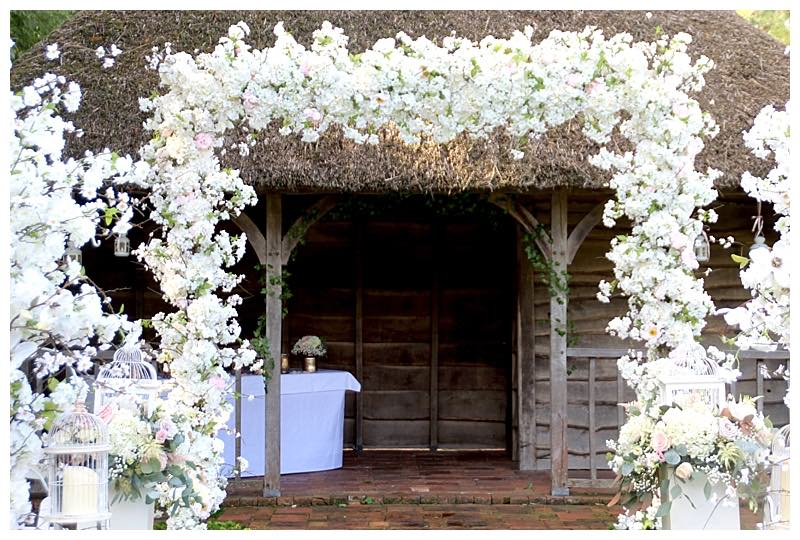 surrey barn wedding flowers arch at Great Fosters in Surrey