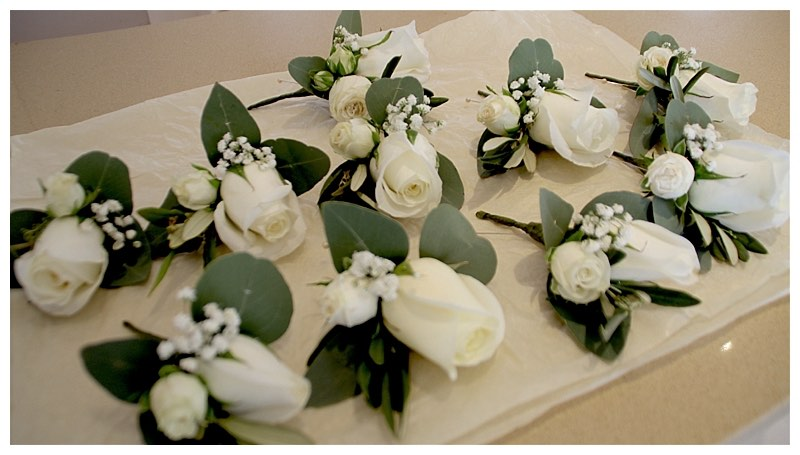 white rose and spray rose buttonhole with gypsophila.
