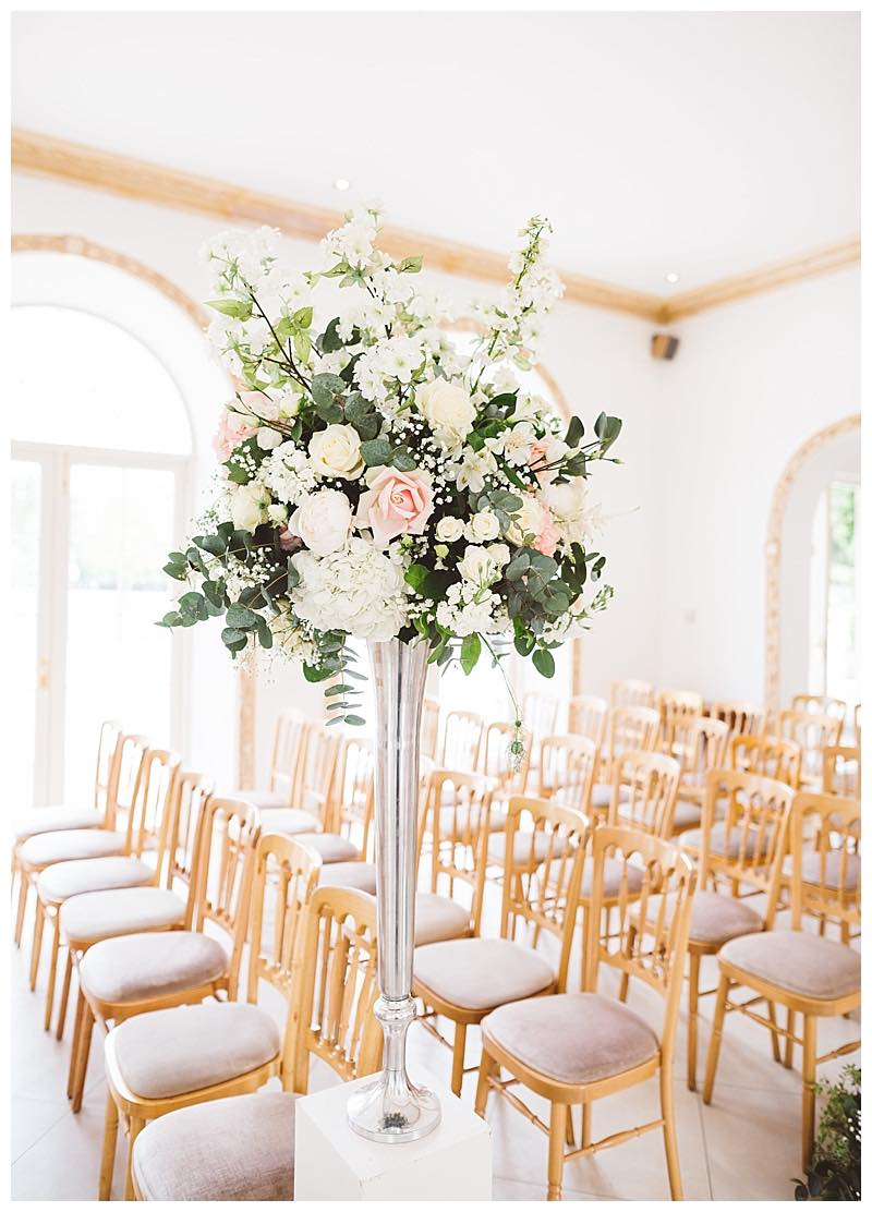 tall silver vase with informal re;axed wedding flowers, using ivory and blush hydrangeas, roses, peonies, blue nigella, cherry blossom and eucalyptus.